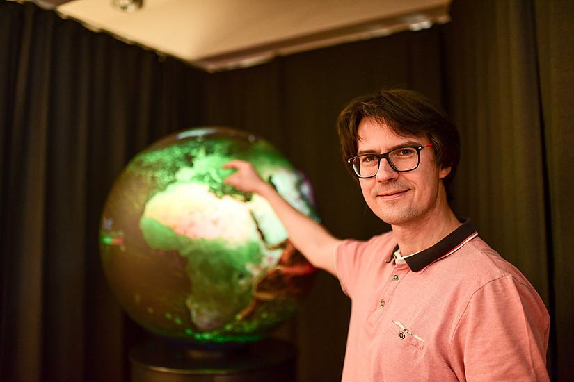 Dort ist Österreich: Martin Mergili zeigt auf die Darstellung am digitalen Globus. Fotos: Uni Graz/Tzivanopoulos