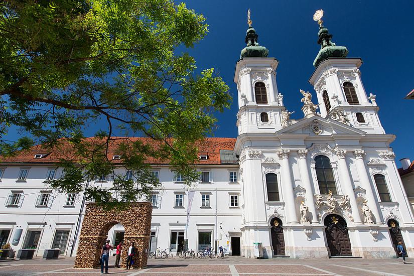 Die Mariahilferkirche in Graz. Teile der Fassadenskulpturen sind werke des Bildhauers Philipp Jakob Straub . Foto: Graz Tourismus/Harry Schiffer