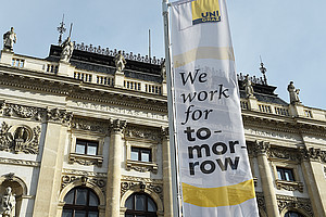 "Hauptgebäude der Uni Graz mit Fahne ""we work for tomorrow"". Foto: Uni Graz/Tzivanopoulos"