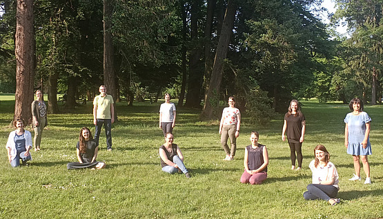 Photo of a part of the researchers of RCIE standing on a green field Copyright RCIE