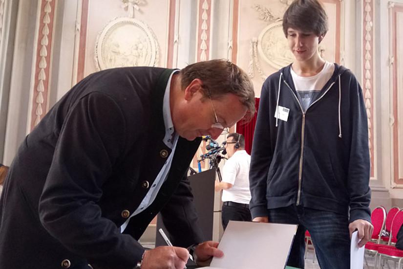 Arnold Hanslmeier signiert Bücher für Preisträger. Foto: IGAM/Maderbacher