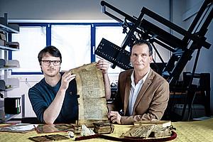Hans Clausen (links) und Karl Lenger machen sich die neuesten Technologie für ihre Forschungen zunutze. Mithilfe spezieller Wellenlängen des Lichts versuchen sie in die Tiefen von alten Schriften zu blicken. Ob das Verfahren fruchtet, sollen nun erste Tests zeigen. Foto: Uni Graz/Konstantinov