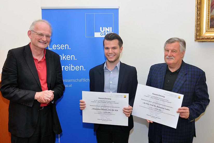 Dekan Lukas Meyer überreicht dem Linguisten Dimitrios Meletis und seinem Betreuer Hanspeter Gadler den Preis.  (v.l.)