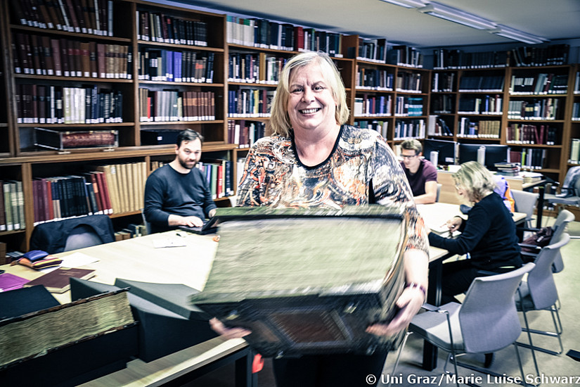 Ute Bergner aus den Sondersammlungen packt schon einmal große Formate weg - bei der Farewell-Feier am 24. Juni könnt ihr die Werke nochmals ansehen. Foto: Uni Graz/Schwarz