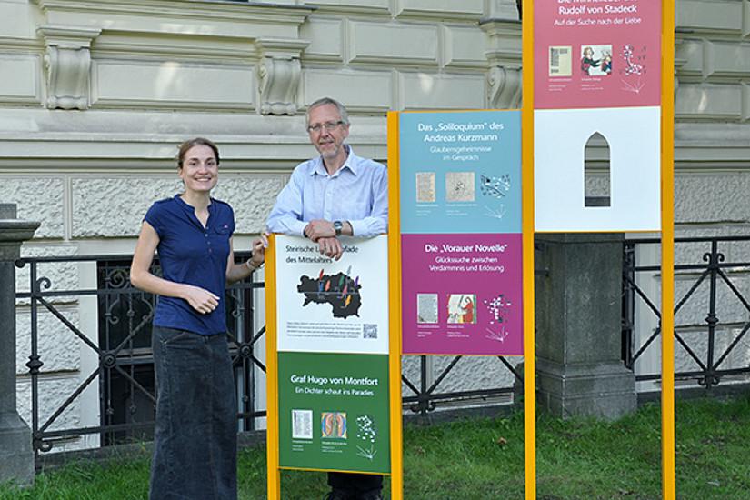 Auch am Campus der Universität Graz haben die Literaturpfade seit 2013 ihren Platz. Vor der Südseite des Hauptgebäudes macht eine Station auf das Projekt aufmerksam. Wernfried Hofmeister mit der Designerin Theresa Zifko. Foto: Uni Graz/Eklaude
