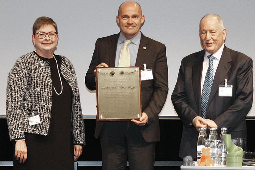 Carolyn Ribes von der IUPAC und Ferenc Darvas, Vorsitzender der ThalesNano and Flow Chemistry Society (r.), überreichten C. Oliver Kappe in Karlsruhe den IUPAC-ThalesNano Prize for Flow Chemistry. Foto: IUPAC