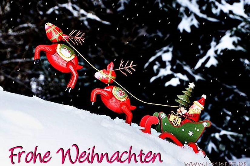Weihnachtsmann mit Schlitten und Rentieren. Schriftzug: Frohe Weihnachten