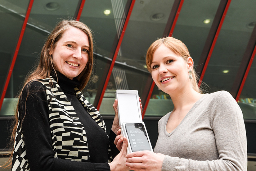 Silvia Rainer (links) überreichte im Namen der Uni Graz das brandneue Smartphone an die Gewinnerin Yvonne Hörzer. Foto: Uni Graz/Tzivanopoulos