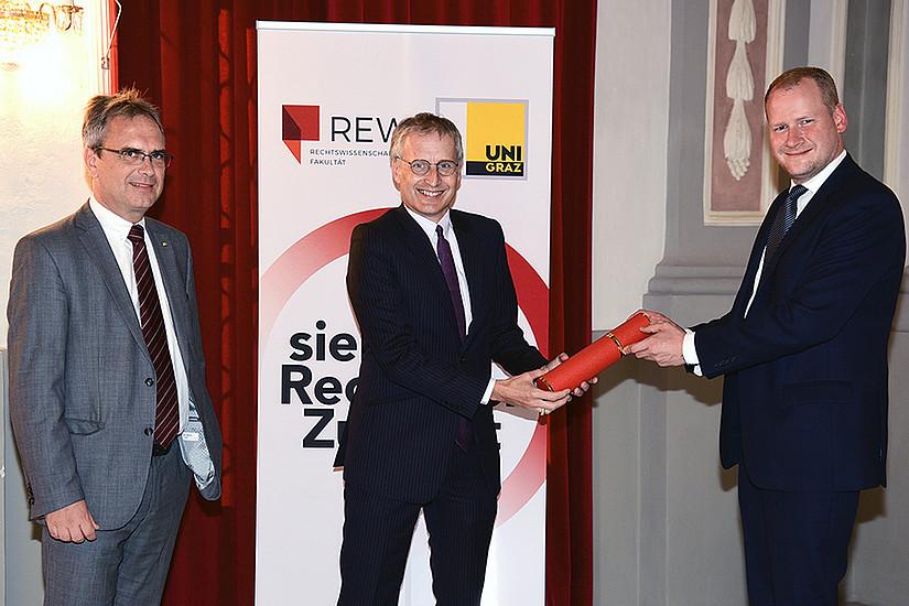 Vizerektor Peter Riedler (links) und REWI-Dekan Christoph Bezemek (rechts) gratulierten Viktor Mayer-Schönberg, der eine Honorarprofessur erhielt. Foto: Uni Graz/Pichler.